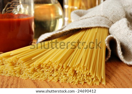 Bundle of uncooked spaghetti on wood counter with sauce and oil in the background.  Macro with extremely shallow dof.  Selective focus on tips of spaghetti.