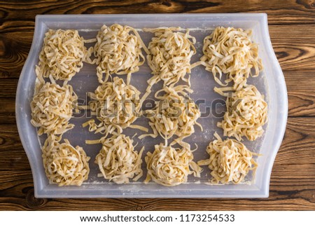 Bundles or portions of fresh fettuccine pasta drying on a white plastic tray on a kitchen table in a home or restaurant viewed from above in a flat lay still life