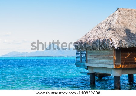 Bungalow over blue water