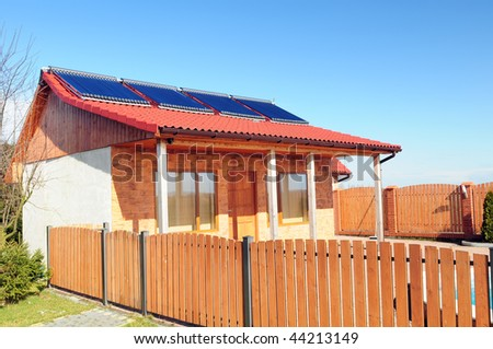 Bungalow with solar panels on the roof and fragment of wooden fence.