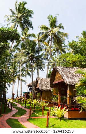 Bungalows and pathway. Vacation background with palm trees