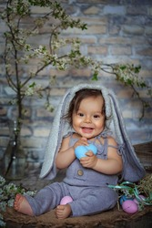 Bunny baby. Cute little boy in rabbit costume sitting on canvas rug with basket blue, pink eggs on brick wall background. Easter holliday concept. Happy child with Easter bunny ears and colorful eggs