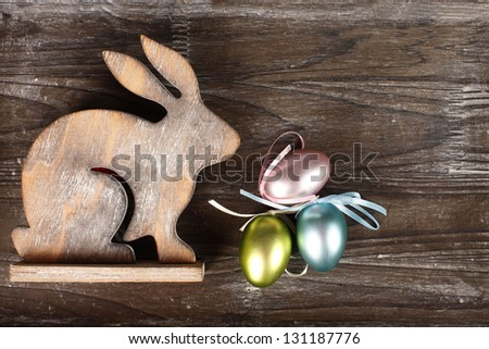 bunny on wooden background with easter eggs