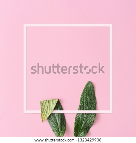 Bunny rabbit ears made of natural green leaves on pastel pink background. Happy Easter minimal concept. Flat lay.