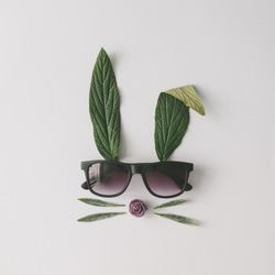 Bunny rabbit face made of natural green leaves with sunglasses on bright background. Easter minimal concept. Flat lay.