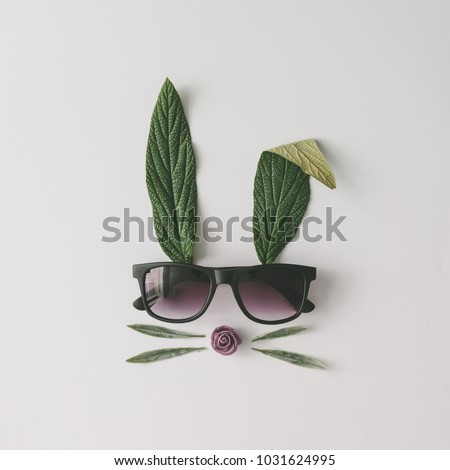 Bunny rabbit face made of natural green leaves with sunglasses on bright background. Easter minimal concept. Flat lay. #1031624995