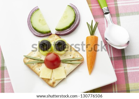 Bunny rabbit made from food with white plate and spoon on table cloth