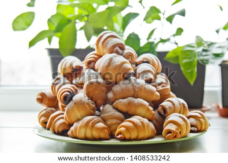 Buns in a plate full of freshly baked bagels sprinkled with powdered sugar on the kitchen table. cooking baking. croissants baking preparation stage. breakfast closeup copy space. #1408533242
