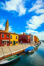Burano is island of multi colored houses near Venice. Inclined tower - landmark of the island of Burano. Boats are parked along the banks of the canals. The concept of cultural and photo tourism