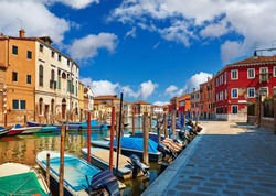 Burano island in Venice Italy over canal with boats among old colourful houses stone streets.