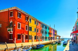 Burano island with colorful houses and buildings on embankment of narrow water canal with fishing boats and view of Venetian Lagoon, Province of Venice, Veneto Region, Northern Italy. Burano postcard