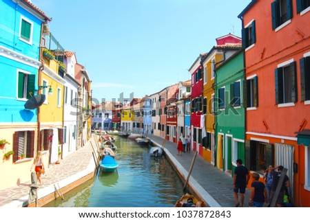 Burano, Italy. Aug 18, 2016. Photographed In Burano, Venice on a sunny day.Boat and Typical brightly painted houses and street in Burano, Italy #1037872843