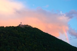 Burg Teck  on a large hill, orange clouds and white moon in the background, trees can be seen as a silhouette, Germany.