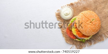Burger and potatoes with sauce. On a wooden background. Top view. Free space for your text. #740519227