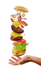 Burger falling into customer's hand. Creative shot of flying ingredients of cheeseburger on white. High fat food.