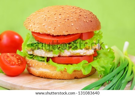 Burger fast food on a kitchen board with tomatoes and green onions