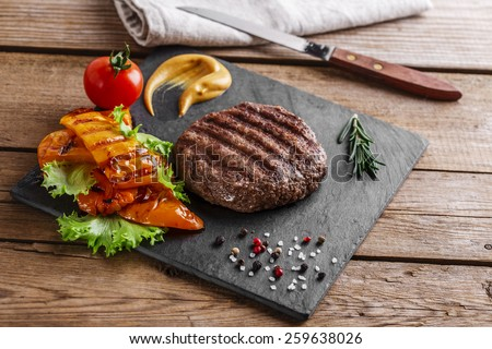burger grill\ with vegetables and sauce on a wooden surface