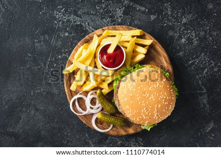 Burger, hamburger or cheeseburger served with french fries, pickles and onion on wooden board. Top view. Fast food concept