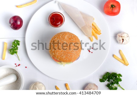 Burger topped with vegetables, spices and fries.  Meat hamburger. Hamburger with knife. Beef hamburger. Organic hamburger