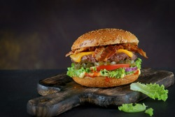 Burger with bacon and cheese on a dark background