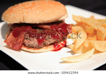 Burger with bacon and fries on a white plate, shot with a shallow depth of field