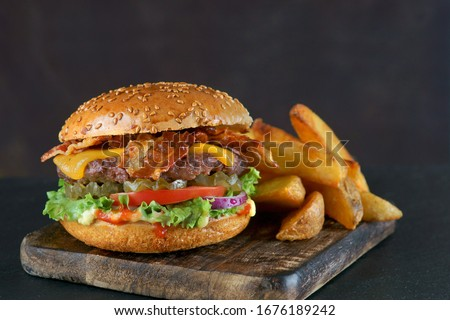 Burger with bacon, cheese and fried potatoes on a dark background