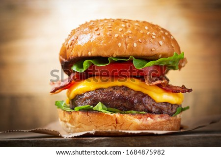 burger with cheese, bacon, salad and vegetables on a wooden  board ストックフォト ©