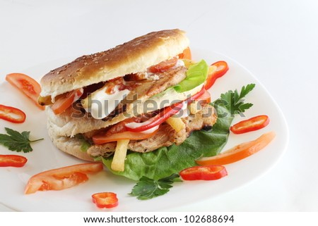 Burger with cheese,lettuce and tomato served on white plate