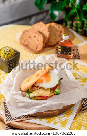 Burger with fried egg, chicken, cheese, tomatoes and other vegetables on a craft paper on yellow background in a restaurant. Toasted black bread on the background. Series of photos for the menu. #1307862283