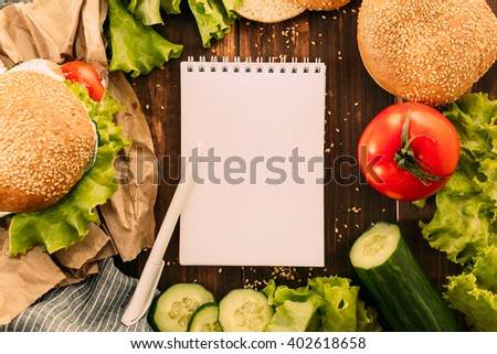 Burger with ingredients and notepad on table #402618658