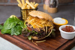 Burger with shoestring fried potatoes and rocket leaves