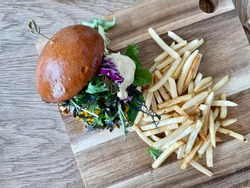 Burger with shoestring fries on the board