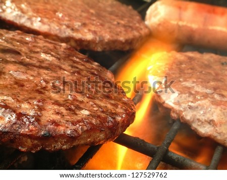 burgers cooking on barbecue over flames
