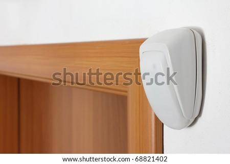 burglar alarm movement sensor on white wall