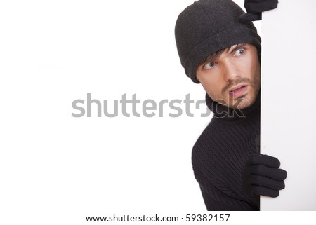burglar in black hat hiding under white board - isolated