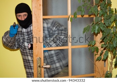 burglar in mask breaking into a house through door, with gun