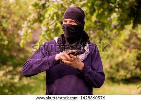 burglar in mask holding and reloading the pistol outdoor #1428860576