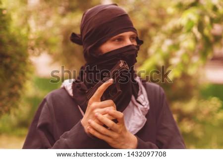 burglar in mask holding and reloading the pistol outdoor #1432097708