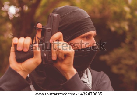 burglar in mask holding and reloading the pistol outdoor #1439470835