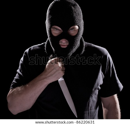 Burglar in mask holding knife on black background