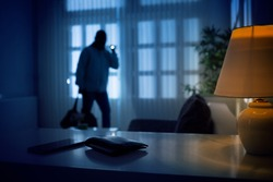 Burglar or intruder inside of a house or office with flashlight