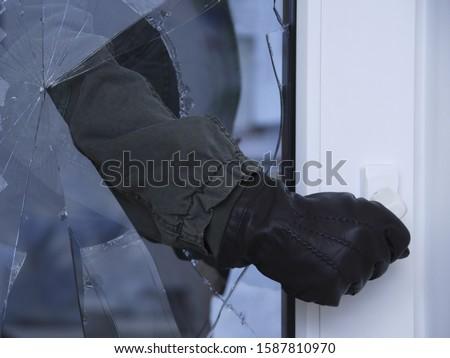 Burglar reaching through broken glass on door Stockfoto ©