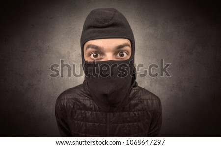 Burglar standing in black clothes and balaclava on his head. #1068647297