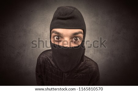 Burglar standing in black clothes and balaclava on his head. #1165810570