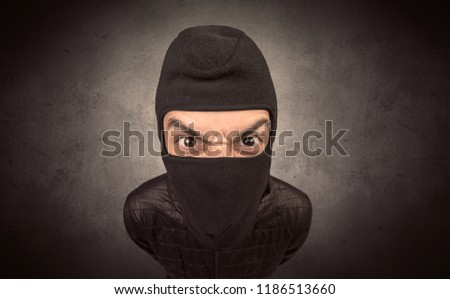 Burglar standing in black clothes and balaclava on his head. #1186513660