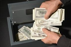 Burglar stealing money from safe box, closeup