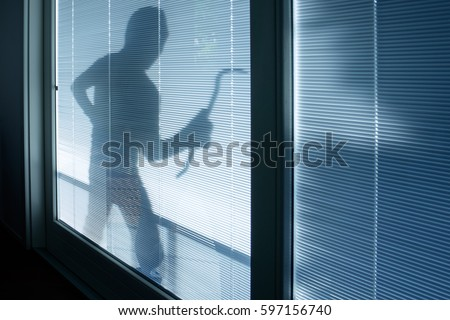 Burglar wearing a balaclava looking through the house window ストックフォト ©