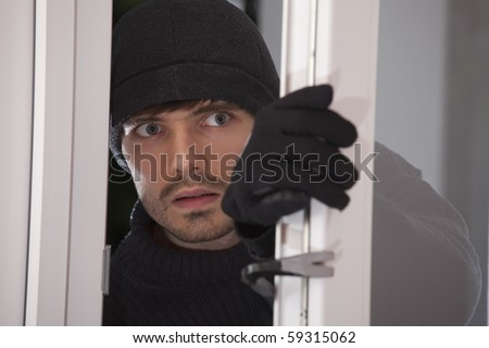 burglar with crowbar breaking into a house through glass door