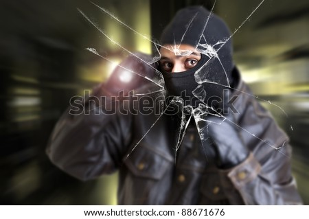 Burglar with flashlight over a broken glass