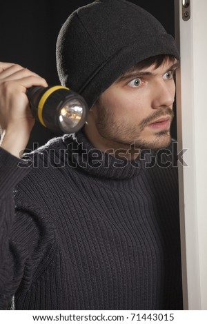 burglar with pocket lamp looking into the room